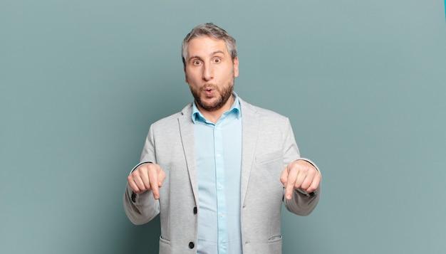 Взрослый бизнесмен с открытым ртом, направленным вниз обеими руками