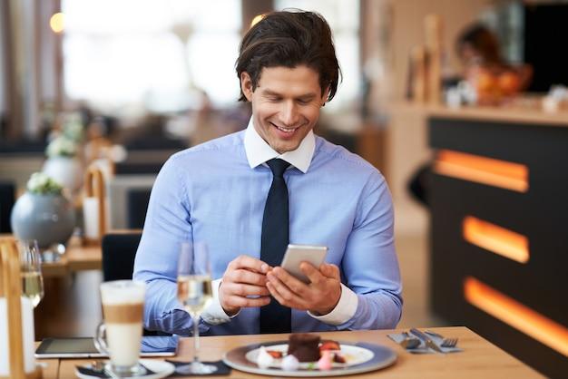 Взрослый бизнесмен со смартфоном на обед в кафе