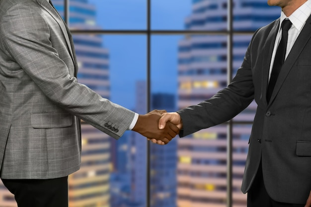 Adult businessmen shake hands. greeting of men in megalopolis. pacified by rules of etiquette. topmanagers at the meeting.