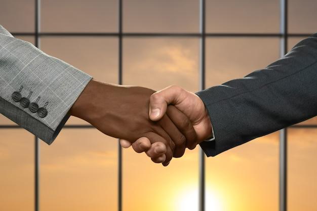 握手する大人のビジネスマン。晴れた空の背景に握手。パートナーシップは単純なものから始まります。正直または欺瞞。