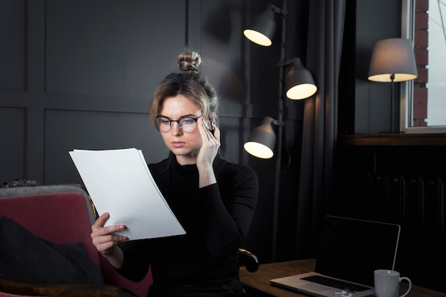 Adult businesswoman looking into papers