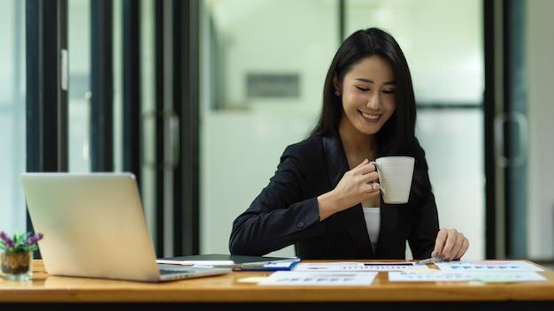 Взрослый бизнесвумен сидит и пьет кофе во время работы в офисе с отчетами и ноутбуком