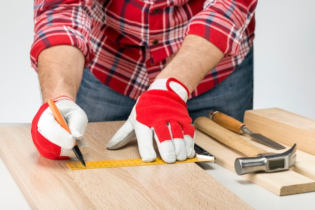 鉛筆を持った大人の大工または職人と大工の正方形が船上に線を引きます。家庭での家具の製造。日曜大工のコンセプト