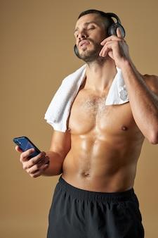 Взрослый кавказский спортсмен со смартфоном в руке, изолированные на желтом фоне