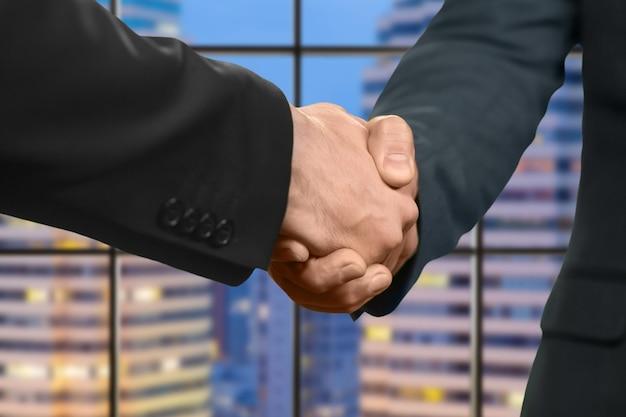 大人の白人ビジネスマンが握手します。夕方のメガロポリスで握手。はじめまして。選挙運動のパートナー。