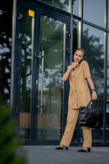 大人の白人の自信を持って若いビジネスウーマンは、現代のオフィスビルの近くの外で電話で話している。