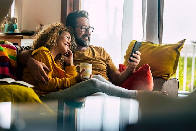 自宅で大人の白人カップルは、友人の人々と技術との電話会議を楽しんでいます