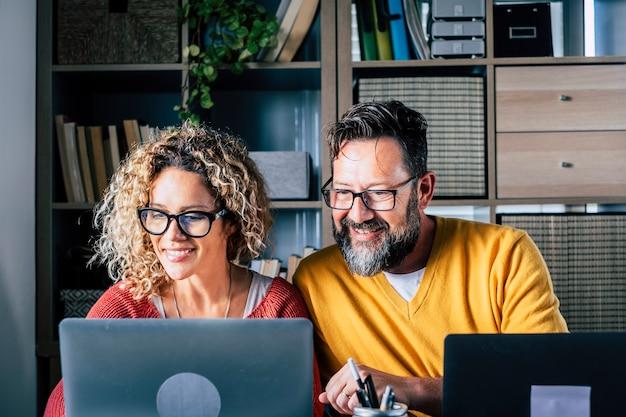 部屋のオフィスの机に座ってスマートワークとリモートワークの仕事の活動で自宅にいる大人の白人カップルは、一緒にコラボレーションを楽しんで、2台のラップトップコンピューターを使用しています-現代のビジネスマン