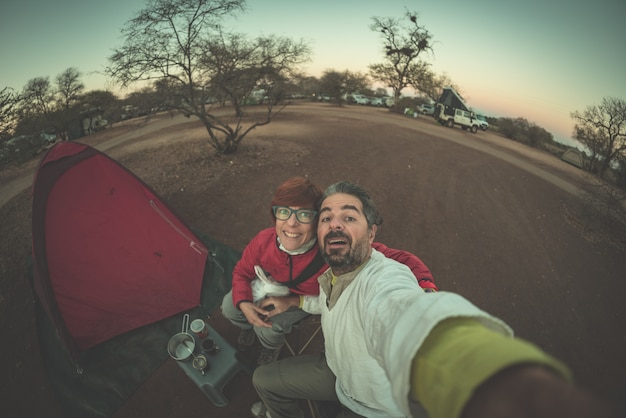 Adult caucasian couple taking selfie in camping site at dusk