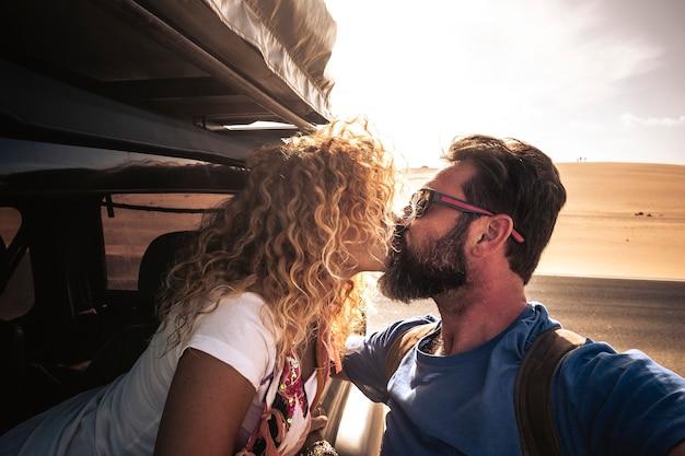 大人の白人のかわいいカップルの旅行者がバックライトで太陽とキスします-愛と関係と一緒に旅行する車-背景と明るい空の砂の砂漠-ひげを持つ男