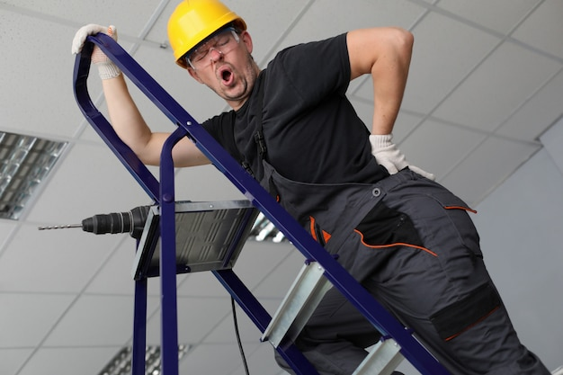 Adult caucasian handyman hold hand on lower