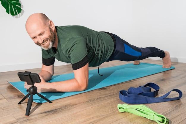 オンライントレーニング中にスマートフォンの前でマットの上に板をやっているスポーツウェアの大人の白人男性。