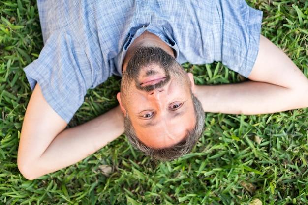Взрослый кавказский человек лежал вверх ногами портрет на траве луг