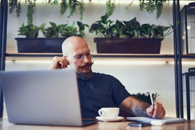 커피를 마시는 카페에서 노트북에 메모를 작성하는 동안 노트북을 사용하는 성인 백인 남자 관리자