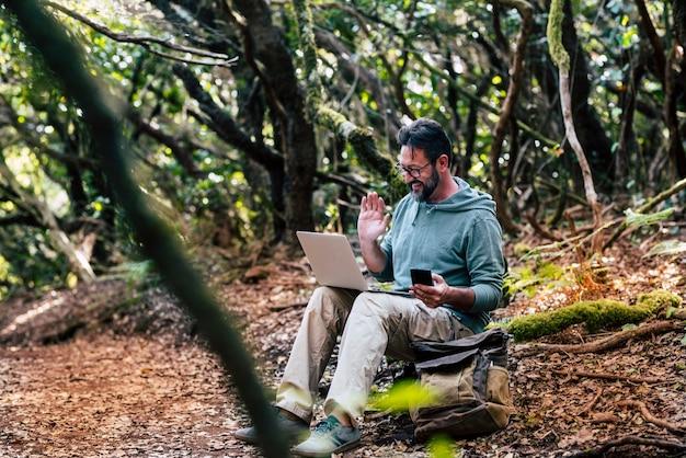 森の地面に座っている大人の白人男性は、ラップトップコンピューターとビデオ通話接続を行います-どこでもインターネットワイヤレスと電話ローミングホットスポットのコンセプト