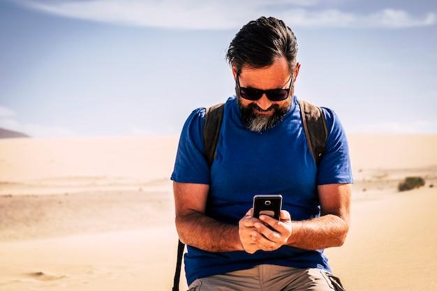 大人の白人男性は砂漠の砂丘砂の真ん中で現代の電話でインターネット接続を使用します