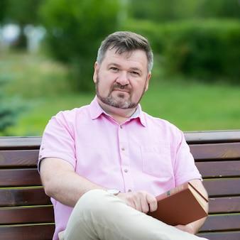 大人の白人男性は彼の手で本を持ってベンチに座っています