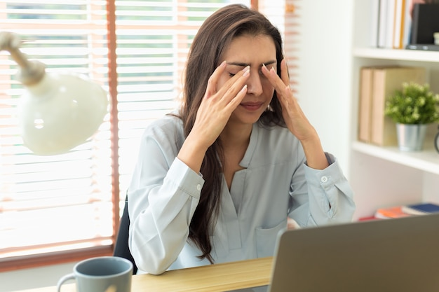 Adult caucasian woman has a headache from working too long at her laptop