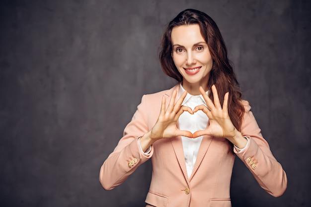 Взрослая женщина кавказской шоу сердца знак на сером темном фоне