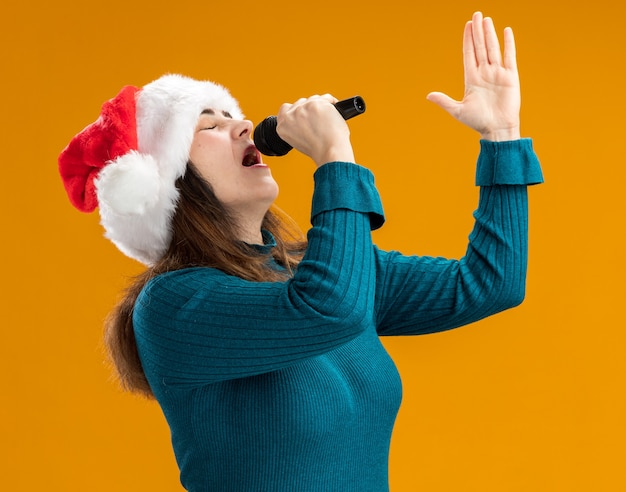 Adult caucasian woman with santa hat holds mic pretending to sing isolated on orange background with copy space