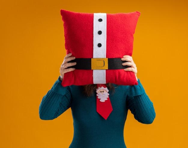 コピースペースとオレンジ色の背景で隔離の顔の前に飾られた枕を保持しているサンタネクタイと大人の白人女性
