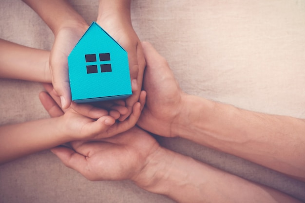 Adult and child hands holding blue paper house for family home and homeless shelter concept