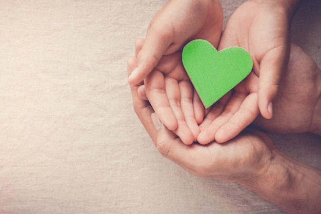 Adult and child hands holding green heart, vegan vegetarian, sustainable living, healthy wellness, csr social responsibility concept, world environment da, world health day