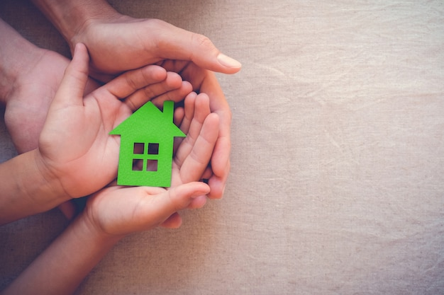 Adult and child hands holding green paper house