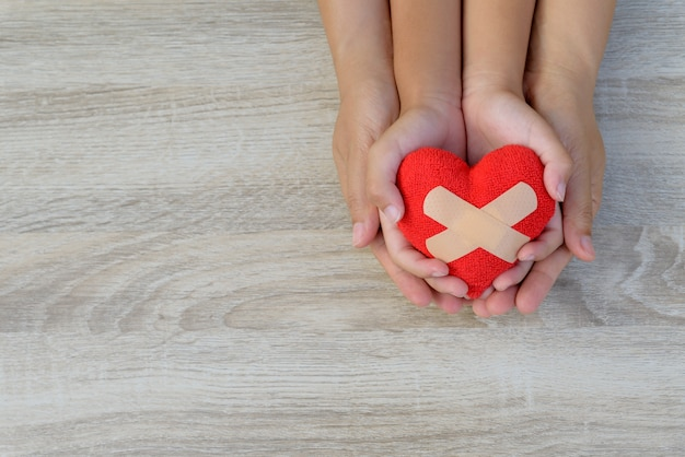 Adult and child hands holding handmade red heart on wooden background.
