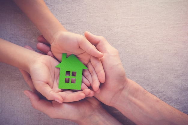 Adult and child hands holding paper eco house, family home, homeless shelter and real esta