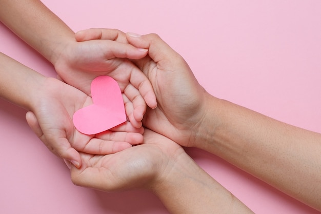 Adult and child hands holding red heart over pink background. love, healthcare, family, insurance, donation concept
