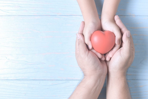 Adult and child hands holding red heart on vintage