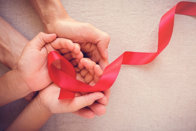 Adult and child hands holding red ribbon, world aids day