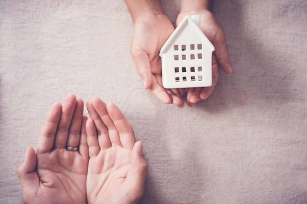 Adult and child hands holding white house, family home and homeless shelter concept