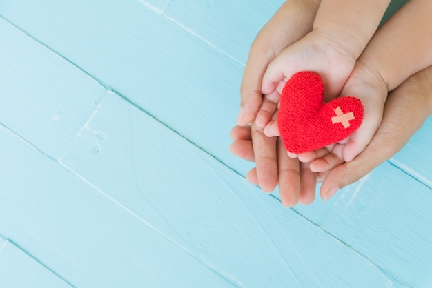 Adult and child holding red heart in hands, love and health care concept.