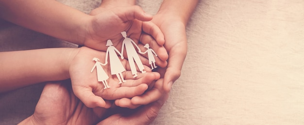 Adult and children hands holding paper family cutout, family home, foster care, homeless support