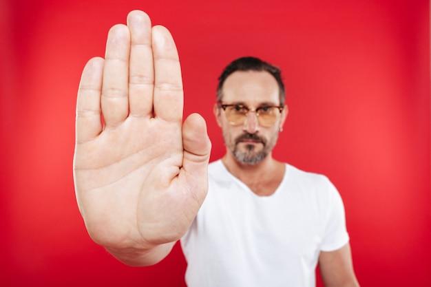 Взрослый концентрированный человек в красочные очки сделать жест остановки.