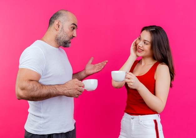 Adult couple both holding cups and looking at each other man telling something to woman and showing empty hand woman smiling and keeping hand on face