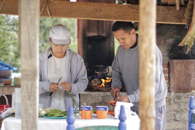 オーブンと屋外のキッチンで燃えている薪を背景に森の中で木製のキオスクの下で白いテーブルクロスとテーブルで食べ物を切り刻む大人のカップル