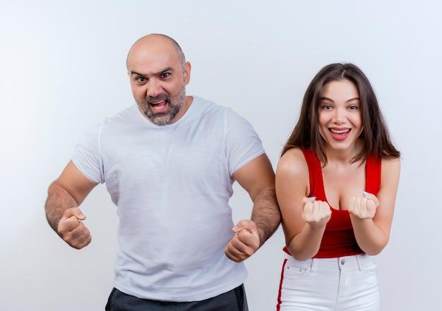 Взрослая пара, уверенный в себе мужчина и радостная женщина и сжимающие кулаки, изолированные на белой стене