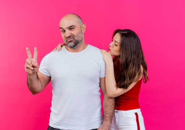 Adult couple confident man doing peace sign looking woman putting hands on man's shoulders doing kiss gesture