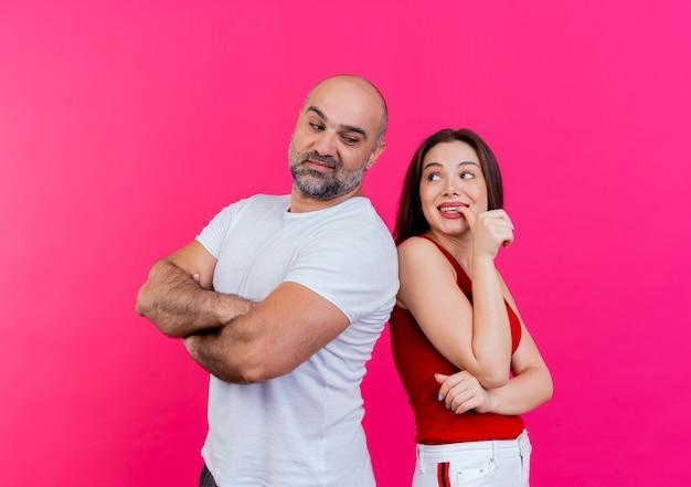 Взрослая пара, уверенный в себе мужчина, стоящий с закрытой позой и впечатленная женщина, кусающая палец, оба смотрят друг на друга