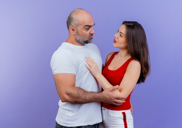 Взрослая пара сомневается, что мужчина кладет руку женщине на спину и касается ее руки, и она кладет руку ему на грудь, глядя друг на друга