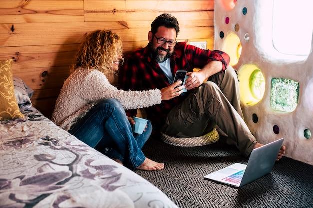 휴대 전화 장치 화면을보고 바닥에 연결된 노트북 인터넷을 사용하여 여행하는 가정이나 호텔에서 기술을 즐기는 성인 부부