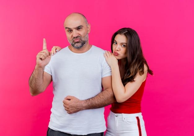 Coppia adulta che aggrotta le sopracciglia uomo rivolto verso l'alto e donna che mette le mani sulla spalla dell'uomo entrambi alla ricerca