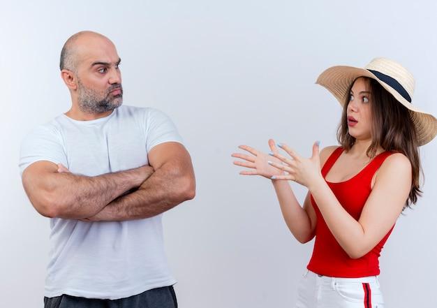 Взрослая пара хмурится мужчина, стоящий в закрытой позе, и впечатленная женщина в шляпе, разводя руками, глядя друг на друга
