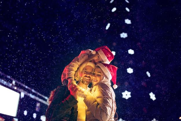 Взрослая пара гуляет в городе во время рождества на фоне огней города и снега ночью