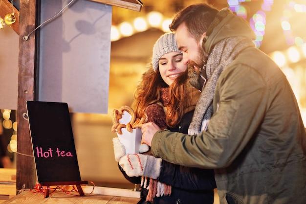 Взрослая пара гуляет в городе во время рождества