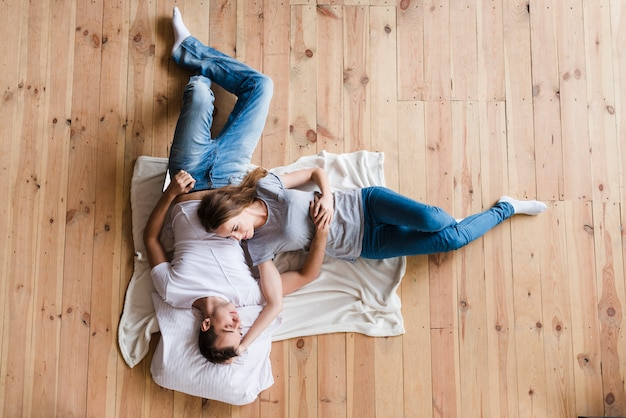 Adult couple hugging on sheet on floor