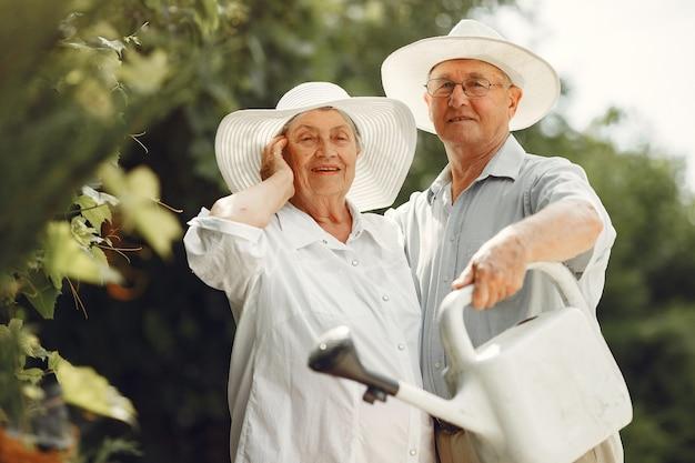 Взрослая пара в летнем саду. красивый старший в белой рубашке. женщина в шляпе. семейный полив.